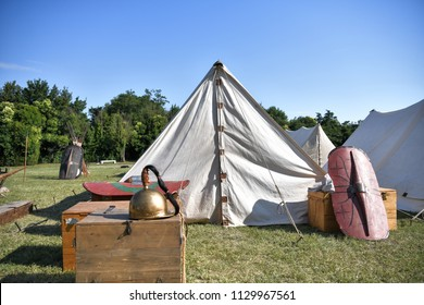 Aquileia, Italy - 17 June 2018: Roman legionary camp with tents, armor shields and a helmet during the Tempora in Aquileia, ancient Roman historical re-enactment