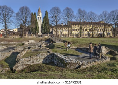 AQUILEIA, ITALY - JANUAR 3, 2010: Tourists visiting the ruins of big roman town Aquileia, Italy