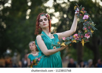 Aquileia, Italy - June 17, 2018: A young woman in traditional ancient Roman dress, dances holding a wreath of flowers during Tempora in Aquileia, ancient Roman historical re-enactment