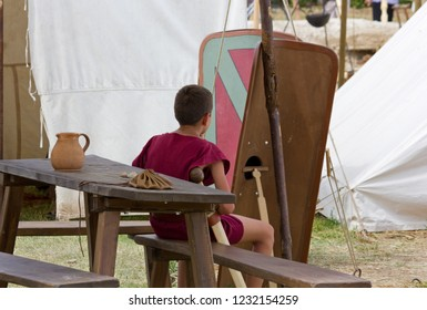 AQUILEIA, Italy - June 22, 2014: A costumed young boy sitting on a wooden bench among tents and shields at the local annual ancient roman historical reenactment