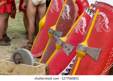 AQUILEIA, Italy - June 22, 2014: A row of decorated legionary shields, a grinder and a few soldiers in an ancient roman encampment during the local annual historical reenactment