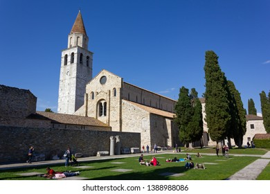 AQUILEIA, Italy - May 1, 2019: The Basilica and its park full of people in a springtime sunny afternoon