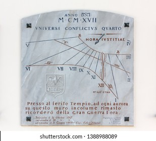 AQUILEIA, Italy - May 1, 2019: Marble sundial on the exterior wall of a building, with italian and latin inscriptions, memorial of the First World War
