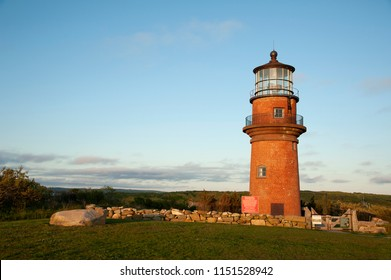 Aquinnah lighthouse, also referred to as Gay Head light, sits on a hilltop, surrounded by a stone wall and wooden gate as the sun sets on Martha's Vineyard island in Massachusetts.