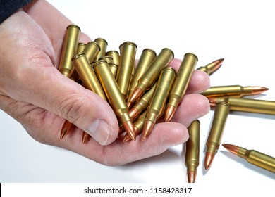 AR 15 full metal jacket ammunition held in a man's hand isolated on white