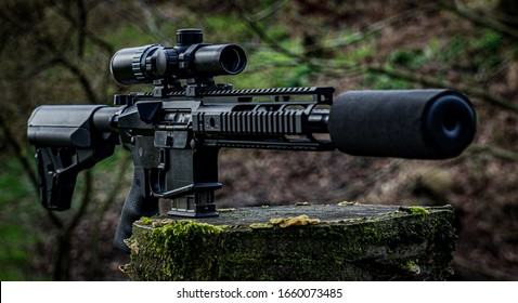 AR15 black assault rifle chambered in 300aac with silencer and scope stand on stump with diffuse green background