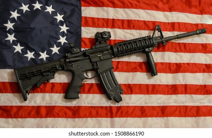 AR15 with red dot and forward grip on Betsy Ross flag