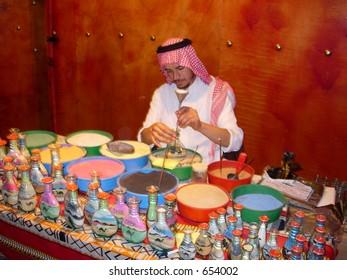 an arab artist making sand bottle souvenir