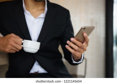 Arab beard businessman play smartphone and carry coffee cup in cafe. Business man chat, surf social media , and check project plan from mobile data using 4g technology.