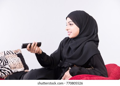 Arab beautiful woman sitting on sofa at home using remote control with white background
