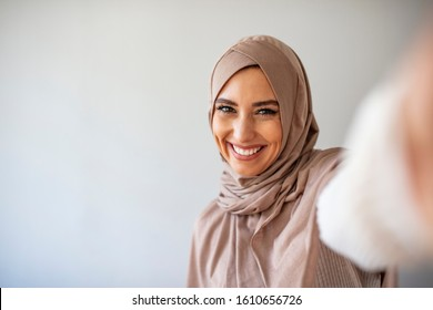 Arab beautiful woman smiling and selfie taking pictures by her mobile phone on gray backgound. Portrait of young muslim woman posing taking selfie photo with mobilephone