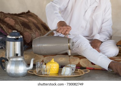 Arab Bedouin Man sits on the floor and pours tea or coffee from teapot into the white cup in Bedouin tent.White traditional Arabic clothing.