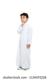 Arab boy with a confused look and his hand on chin, looking up, wearing white traditional Saudi Thobe and sneakers, raising his hands on white isolated background