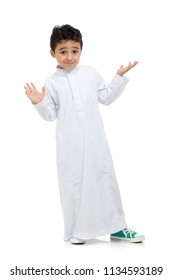 Arab boy confused, wearing white traditional Saudi Thobe and sneakers, raising his hands on white isolated background