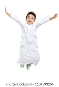 Arab boy jumping high with a big smile and open eyes, wearing white traditional Saudi Thobe and sneakers, on white isolated background