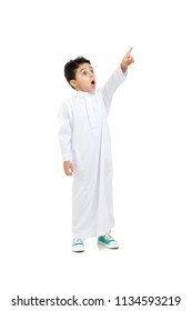 Arab boy looking at far and pointing his finger with a big surprise on his face, wearing white traditional Saudi Thobe and sneakers, raising his hands on white isolated background