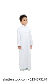 Arab boy looking at far, wearing white traditional Saudi Thobe and sneakers, raising his hands on white isolated background