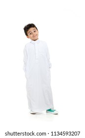 Arab boy relaxed and smiling with raised eye brows, wearing white traditional Saudi Thobe and sneakers, raising his hands on white isolated background