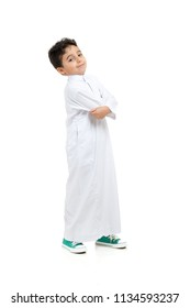 Arab boy smiling and acting cool with crossed hands, wearing white traditional Saudi Thobe and sneakers, on white isolated background
