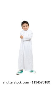 Arab boy smiling and crossing hands, wearing white traditional Saudi Thobe and sneakers, on white isolated background
