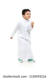 """Arab boy with a """"yes"""" victory expression on his face, wearing white traditional Saudi Thobe and sneakers, raising his hands on white isolated background"""
