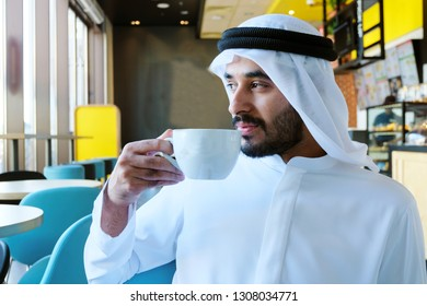 Arab business man drinking coffee at a cafeteria wearing kandoora