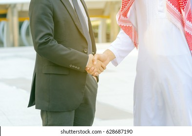 Arab business man hand shaking,standing,city background,business success concept,copy space.