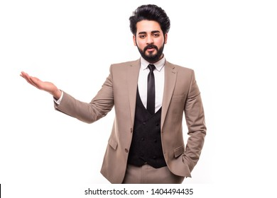 Arab business man presenting something in the back with one hand in his pocket while looking at the camera on white background