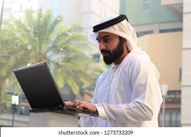 Arab Business Man Using Internet Outside The Office Near Palm Trees, Wearing UAE Emirati Dress ( INTERNET WIFI LAPTOP TECHNOLOGY )