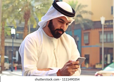 Arab Business Man Wearing UAE Traditional Dress Using Mobile Phone  ( Smartphones Wi Fi Internet )