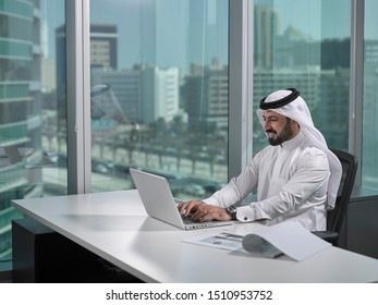 Arab business man woking in a modern office wearing traditional attire