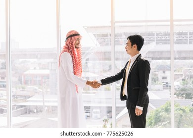 Arab Business Partners with Asian Partners After a successful business deal.Two businessman shake hand as a greeting.
