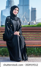 Arab businessman. Arab businesswoman hijab sitting on the bench on the background of skyscrapers in Dubai while smiling and looking directly at the camera. The woman is dressed in a black abaya