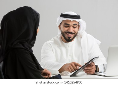 Arab businessman and businesswoman using digital tablet.
