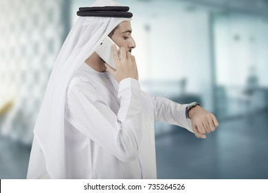 Arab businessman delayed checking the time in the watch while he is making a telephone call with his mobile phone