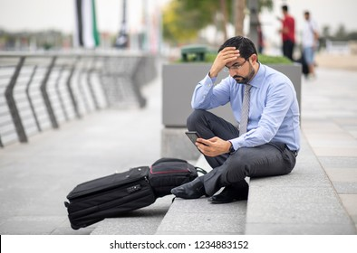 arab businessman with his suitcase in a city, sitting on stairs and looking at his phone