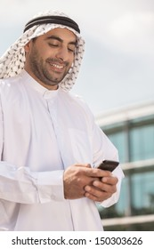 Arab businessman with mobile phone. Confident Arab businessman holding his mobile phone and smiling