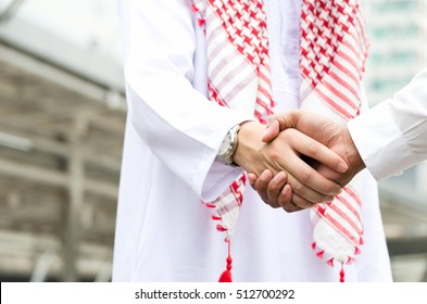 Arab businessman shake hand with Asian partner. Business people shake hand as a business agreement successful. Two businessman shake hand as a greeting outdoor