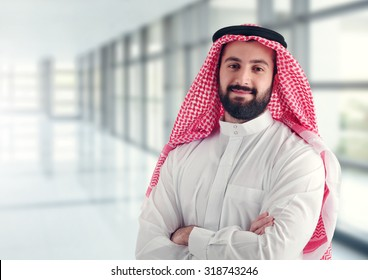 Arab businessman standing in a modern hallway with his arms crossed