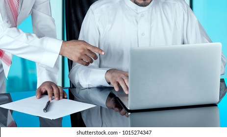 Arab Businessmen at Disk Working on a Laptop