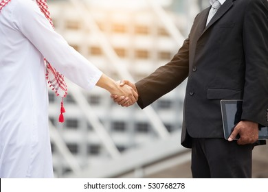 Arab businessmen's handshake partnered with American businessman descent. Confirmation of business alliance partners as well.Adhering respect, commitment and integrity in business.partnership deal