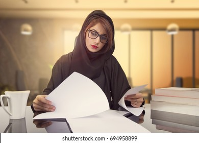 Arab businesswoman revising company financial results. reading document  at workplace. Female office worker satisfied with market analysis, financial forecast