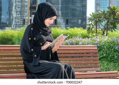 Arab businesswoman typing on the tablet while sitting in the city park