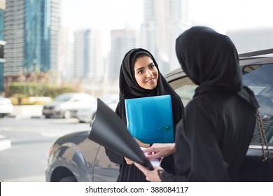 Arab Businesswomen Discuss Something next to a Car