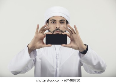 Arab casual man showing a mobile phone isolated on a white background, wearing Emirati style