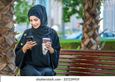 Arab coffee and cell phone. Arab businesswomen in hijab holding coffee outdoors and reading a message on a cell phone against and looking at the camera. The woman is dressed in a black abaya