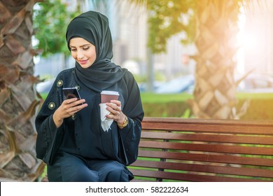 Arab coffee and cell phone. Arab businesswomen in hijab holding coffee outdoors and reading a message on a cell phone and looking at the camera. The woman is dressed in a black abaya