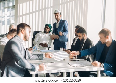 Arab construction CEO in white national candura and gutra on head revising estimate for infrastructure repairs with his multirucial male managers during meeting at desk in office.