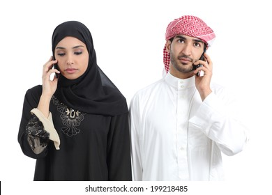 Arab couple disgusted on the phone isolated on a white background