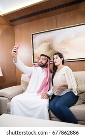 Arab couple at home sitting in raditional dress using mobile phone